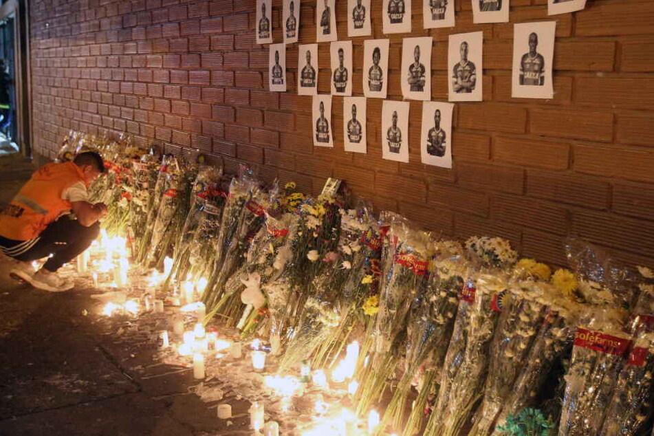 Die Bilder der Spieler an einer Wand, darunter viele Blumen und Kerzen.