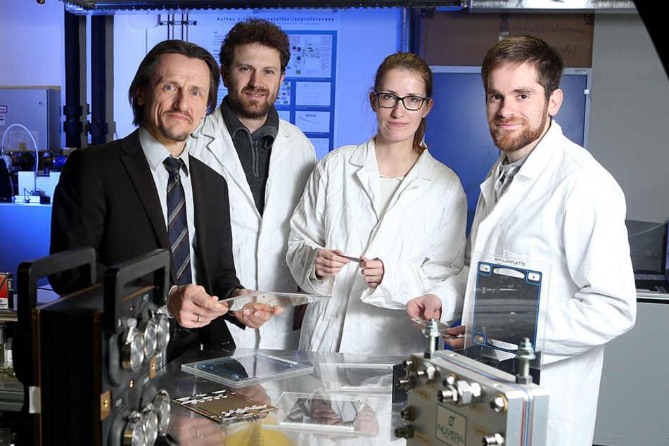 TU-Professor Thomas von Unwerth erklärt Forschern das Modell einer Brennstoffzelle.