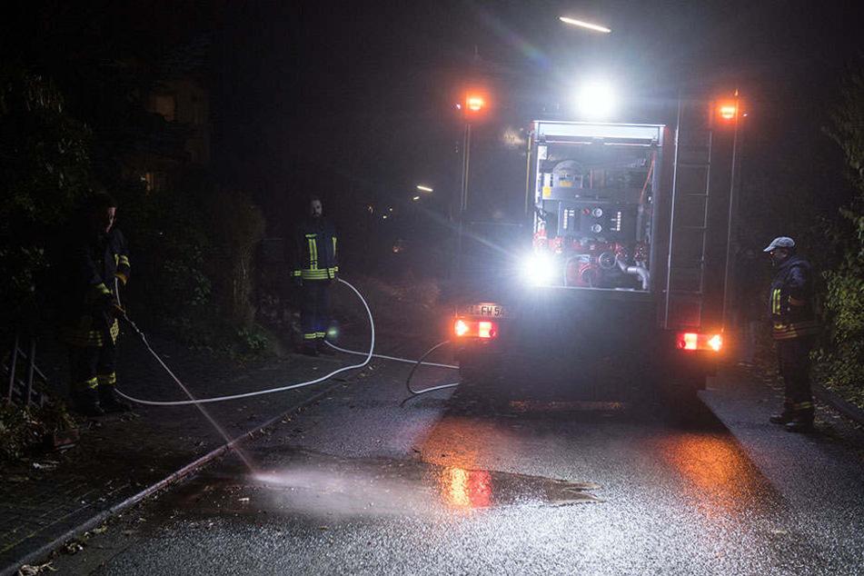 Feuerwehrmänner reinigen die Straße in der Nähe des Tatorts.