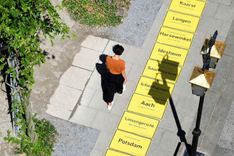 Die gelben Ortstafeln werden probeweise auf einem Berliner Gehweg ausgelegt.