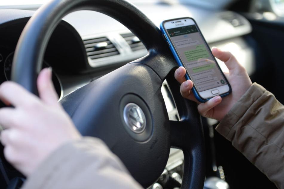 Eine Frau sitzt im Auto am Steuer und liest Nachrichten auf ihrem Smartphone.