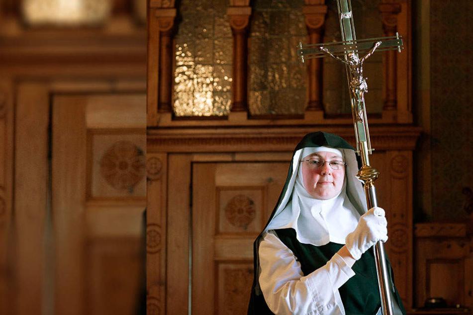 Für die Osternacht bringt die Ordensfrau das Prozessionskreuz aus der Sakristei in die Kirche.