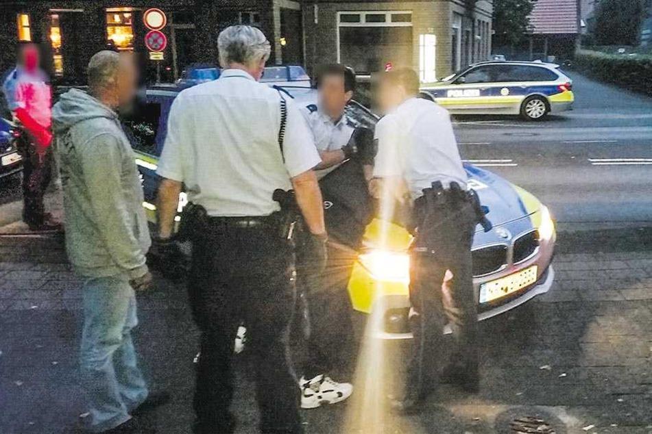 Polizisten fixieren den Mann auf der Motorhaube des Streifenwagens.