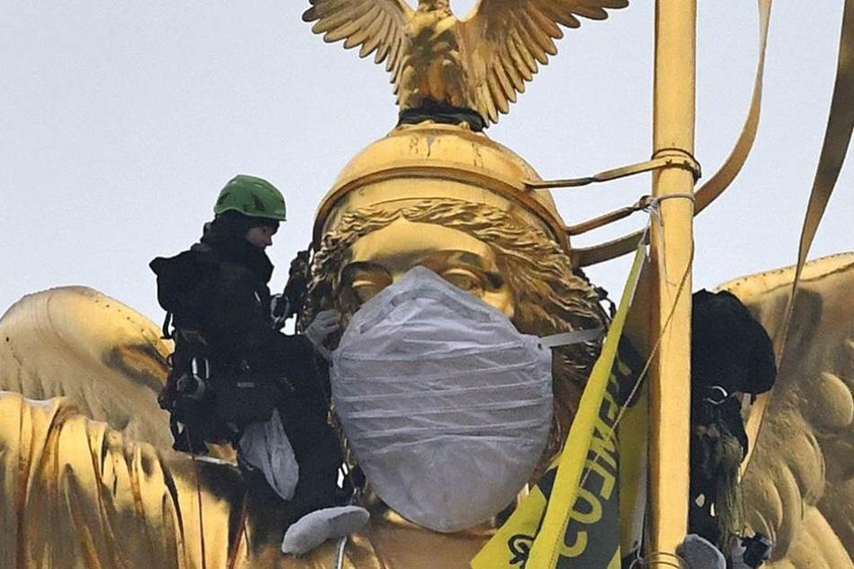 Greenpeace-Aktivisten schnallen dem Mundschutz an der Viktoria fest.