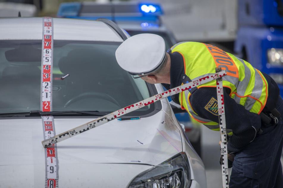 Der Unfallwagen wird von der Polizei untersucht.
