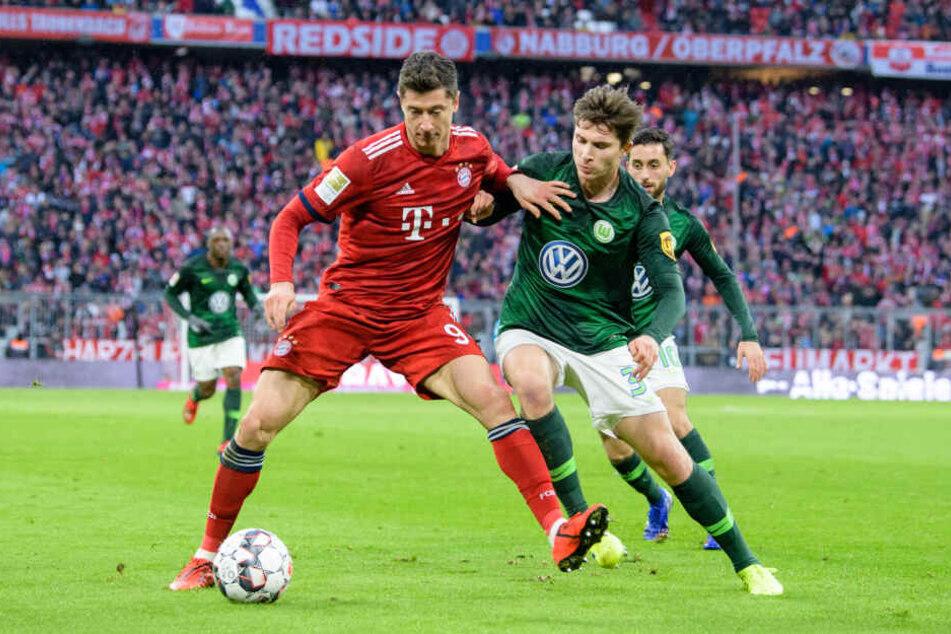 Robert Lewandowski vom FC Bayern München (l) und Elvis Rexhbecaj vom VfL Wolfsburg im Zweikampf um den Ball.