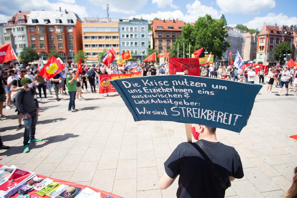 """Ein Demonstrant hält ein Plakat mit der Aufschrift """"Die Krise nutzen um uns ErzieherInnen eins auszuwischen? Liebe Arbeitgeber: Wir sind Streikbereit"""" während der Kundgebung auf dem Stuttgarter Marienplatz."""