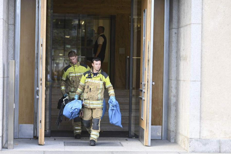 Feuerwehrleute tragen blaue Säcke aus dem Landtag.