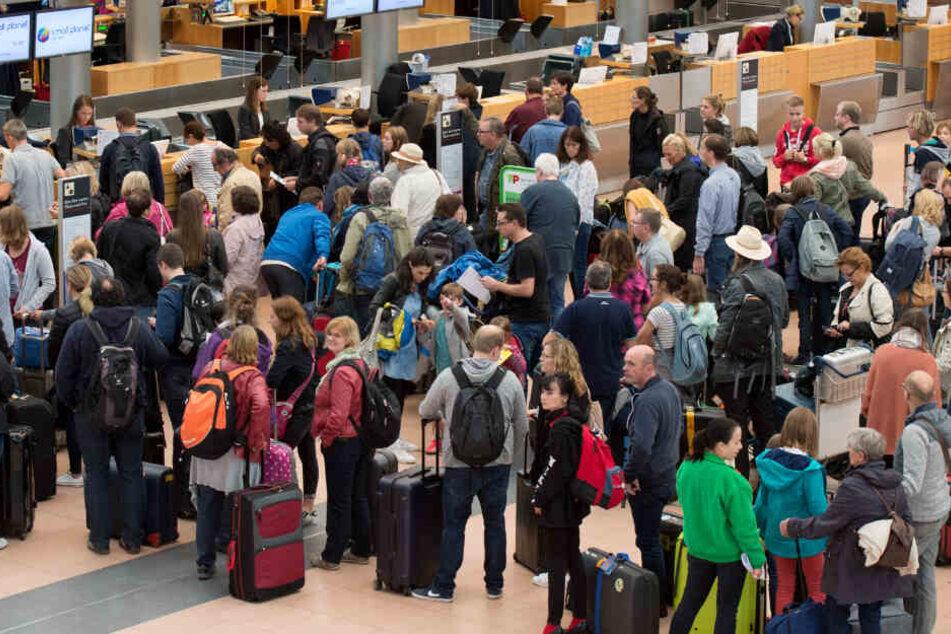 Zahlreiche Fluggäste warten auf dem Flughafen Hamburg vor Abfertigungsschaltern. (Archivbild)