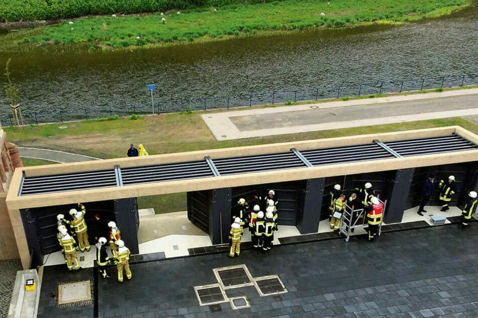 Bei der Hochwasserübung in Grimma schließen Feuerwehrleute die fünf Tore an der erst kürzlich fertiggestellten Pergola am Gymnasium.