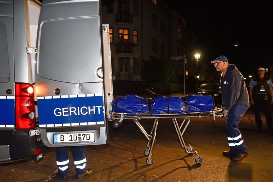 Mitarbeiter der Gerichtsmedizin transportieren denLeichnam zu ihrem Fahrzeug.