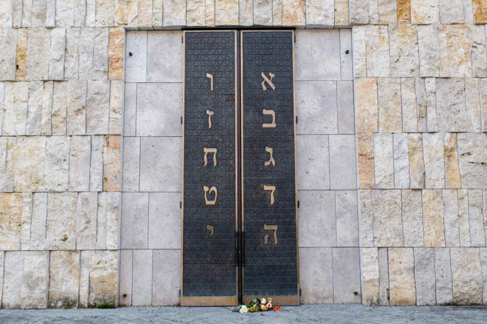 Menschen haben Blumen vor dem Eingangsportal der Münchner Hauptsynagoge Ohel Jakob abgelegt.
