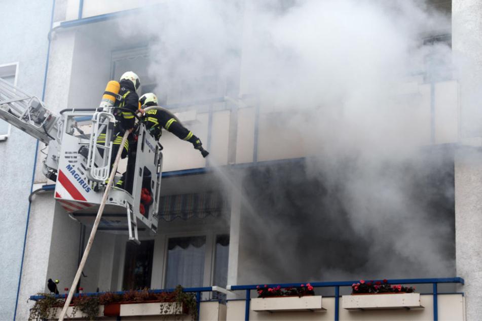 Feuerwehrmänner löschen den Balkonbrand in dem Rostocker Wohnhaus.