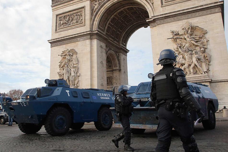 Polizisten und Räumpanzer stehen vor dem Triumphbogen in Paris.