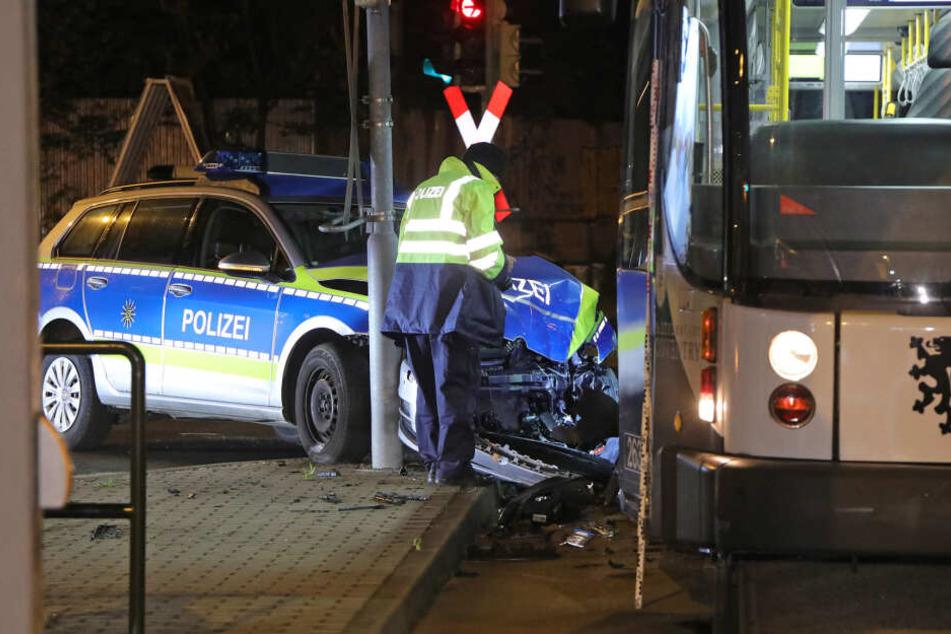 Ein Mitarbeiter der Polizei steht am Polizeiwagen, der in die Bahn krachte.