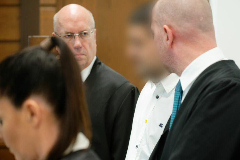Der Angeklagte steht umgeben von seinen Anwälten Jordana Wirths, Christof Miseré und Martin Bücher (r) im Landgericht in einem Saal.