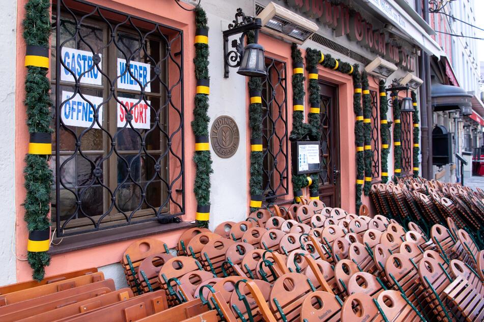 Tische und Stühle stehen vor einem geschlossenen Restaurant in der Münchner Innenstadt.