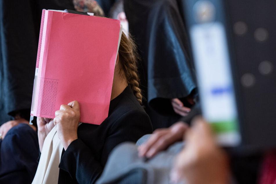 Eine der angeklagten Prostituierten versteckte sich beim Prozessauftakt hinter einer Akte.