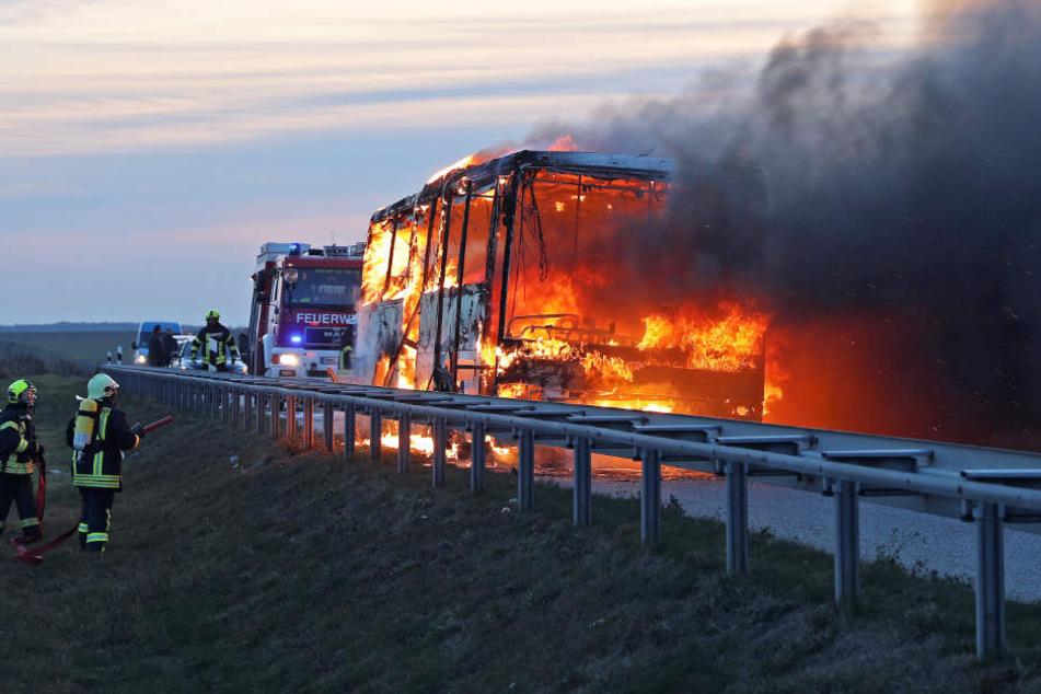 Dunkler Rauch steigt über dem brennenden Bus auf.