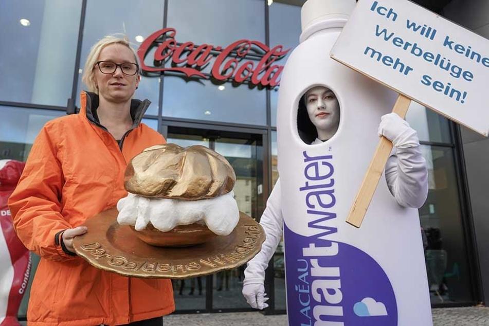 """Eine Mitarbeiterin von Food Watch verleiht vor der Deutschland-Zentrale der Coca-Cola GmbH symbolisch """"Goldener Windbeutel"""" an die Firma Coca-Cola für ihr Produkt """"Smartwater""""."""