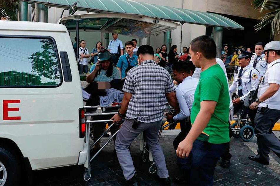 Manila: Rettungskräfte tragen eine Frau zu einem Krankenwagen, nachdem ihr schwindlig wurde.