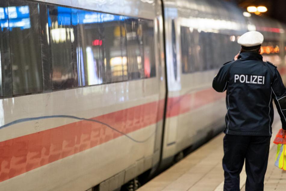 Ein ICE steht im Hauptbahnhof einer deutschen Großstadt, während daneben ein Polizeibeamter telefoniert.