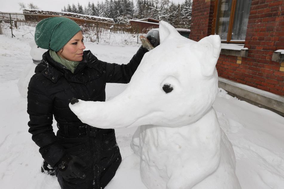 Steinbildhauerin, Jenny Lux steht neben einer ihrer Schneefiguren. Sie hat diese Figuren in der saisonbedingten Winterpause aus einer Laune heraus gebaut.