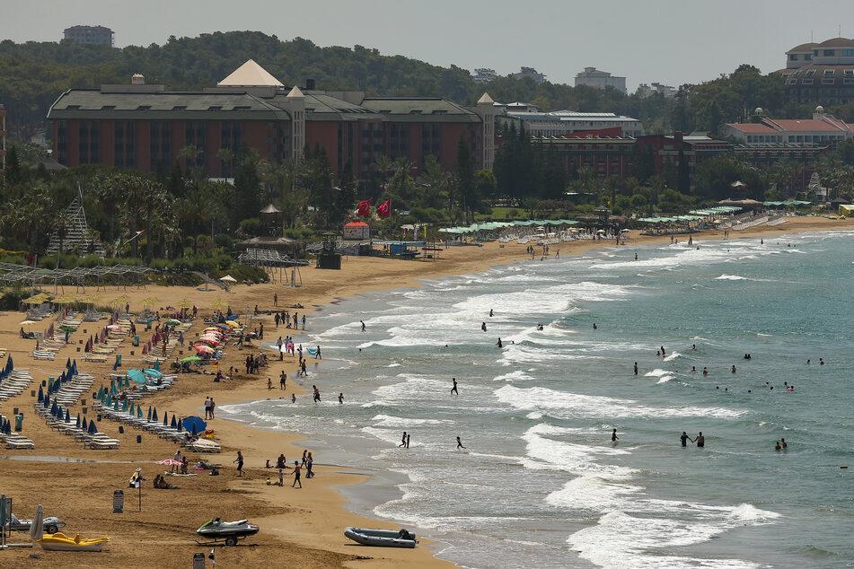 Touristen besuchen den Strand von Antalya. Die Bundesregierung stuft die Türkei als Corona-Hochrisikogebiet ein.