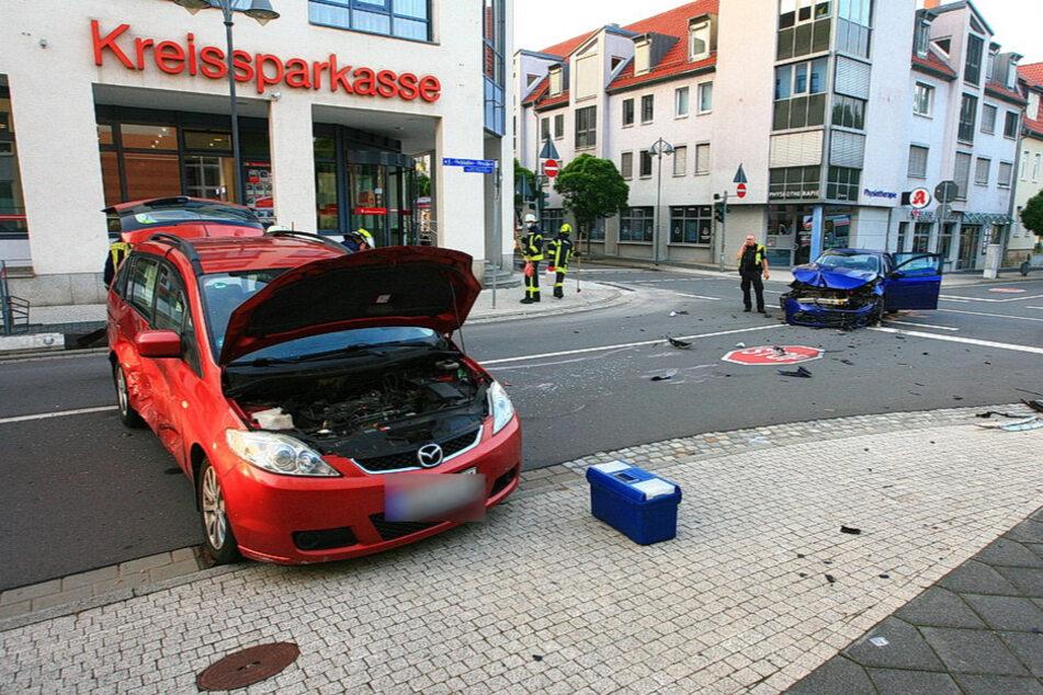 Der Mazda und Peugeot stehen stark beschädigt am Unfallort.