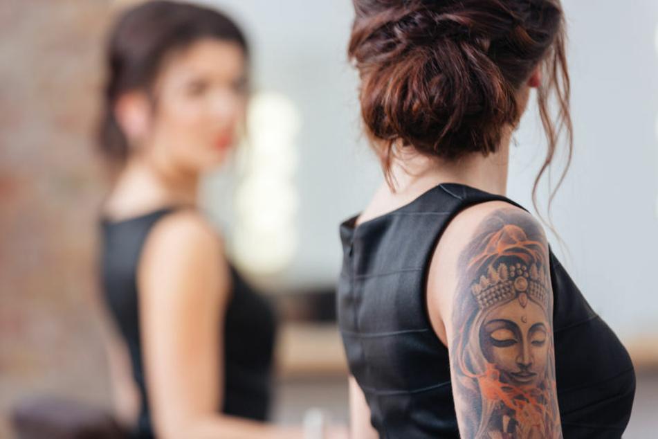 Eine Frau mit Tätowierungen sieht sich im Spiegel an. Claire Shepherd versteht nicht, warum Mitarbeiter nicht auch Tattoos tragen dürfen. (Symbolbild)