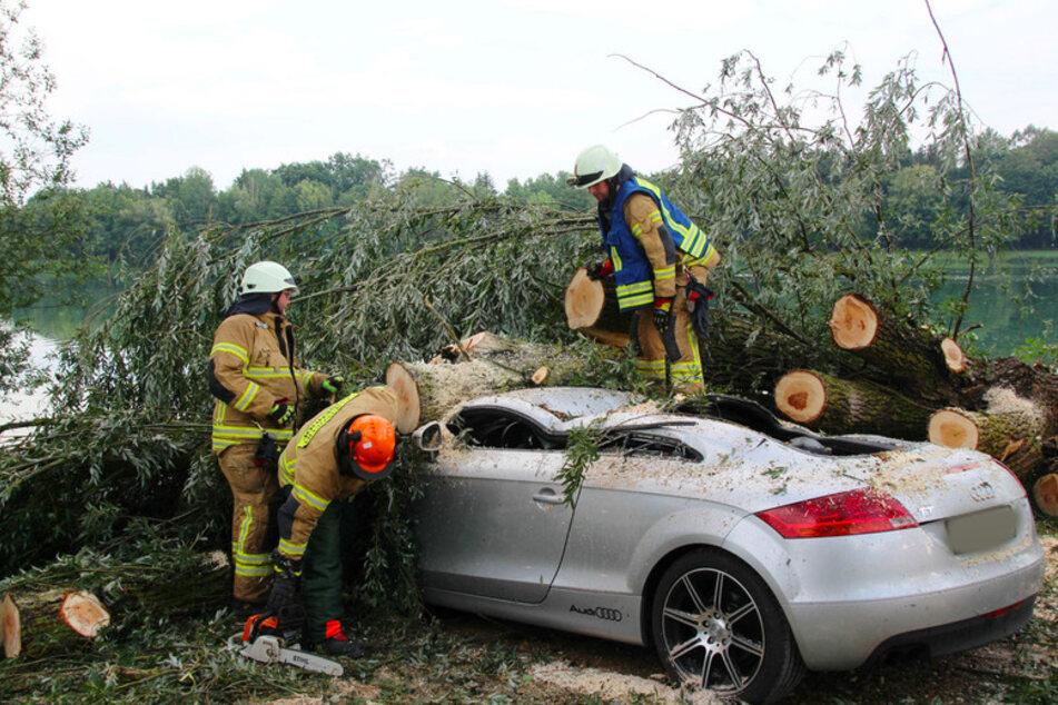 Feuerwehrleute zersägen einen Baumstamm, der am Roither See auf ein Auto gefallen ist.