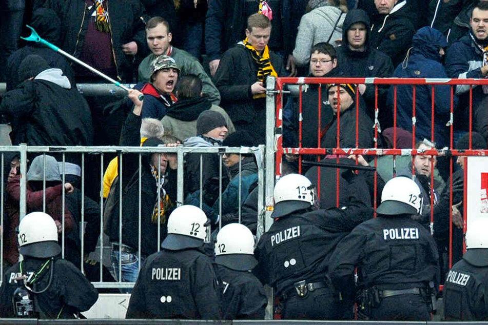 Ein Dynamo-Fan schlägt mit einer Krücke zurück, nachdem die Polizei Pfefferspray in den Dresdner Block gesprüht hatte.