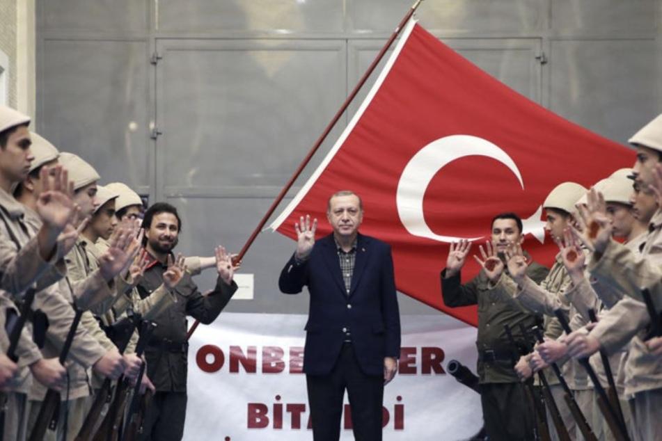 In der Türkei zeigt der Präsident bei jeder Gelegenheit den Rabia-Gruß. Hier mit Soldaten, die ebenfalls mitmachen.