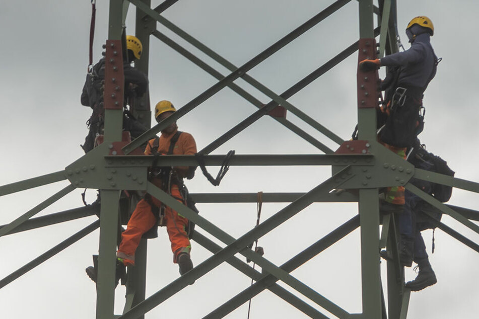 In luftiger Höhe bauen die Monteure Masten für Hochspannungsleitungen zeitgleich auf und ab.