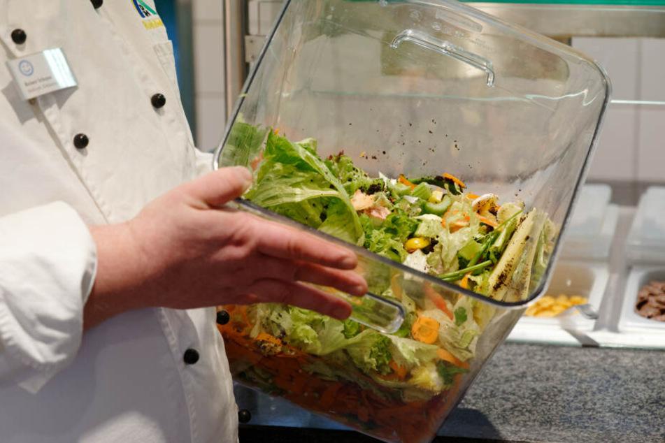 Koch Reiner Schoppen hält in einer Jugendherberge einen Behälter mit Speiseresten.