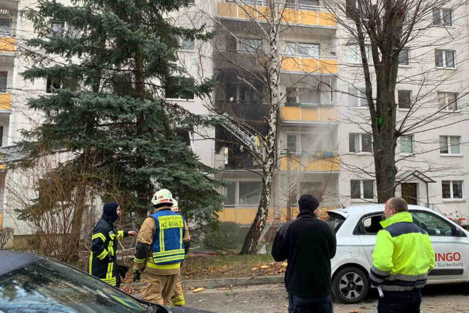Die Feuerwehr löscht Brandreste am Mehrfamilienhaus ab.