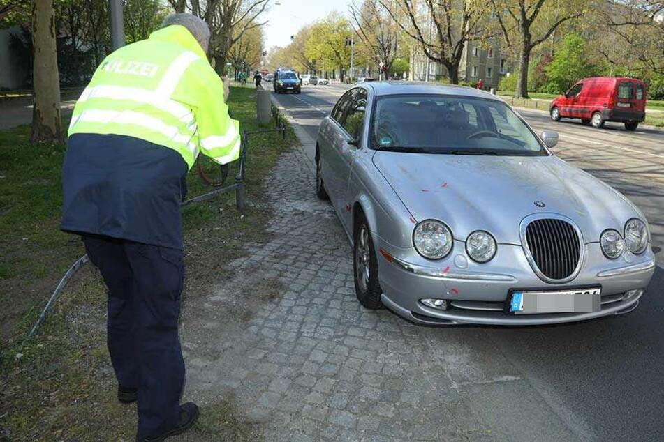 Ein Polizist macht Aufnahmen von dem Unfall-Auto.
