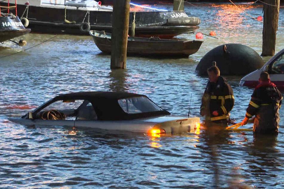 Die Einsatzkräfte stehen hüfttief vor einem geparkten Auto im Wasser.