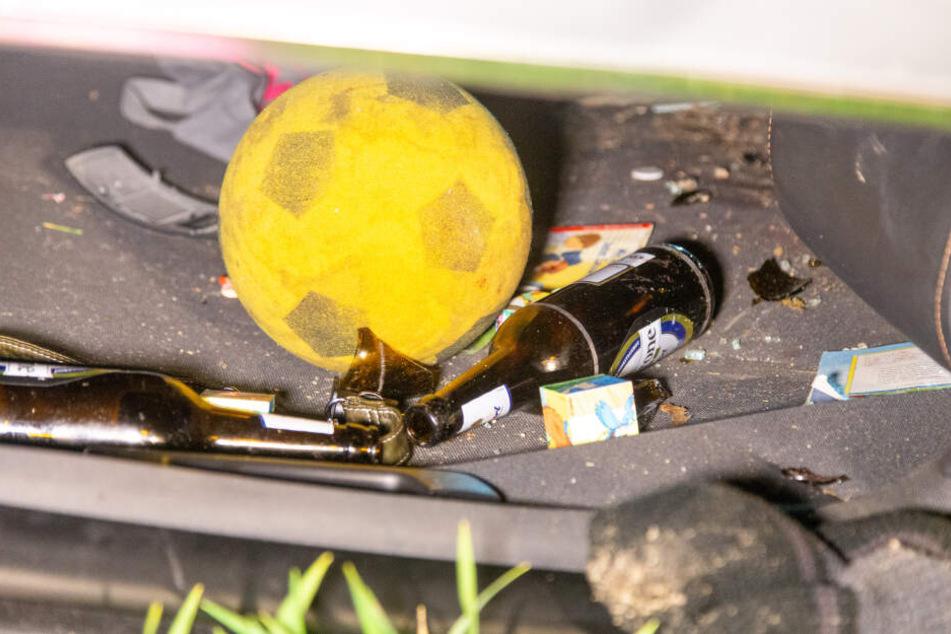 Neben dem Kinderspielzeug lagen überall leere Bierflaschen in dem Auto umher.