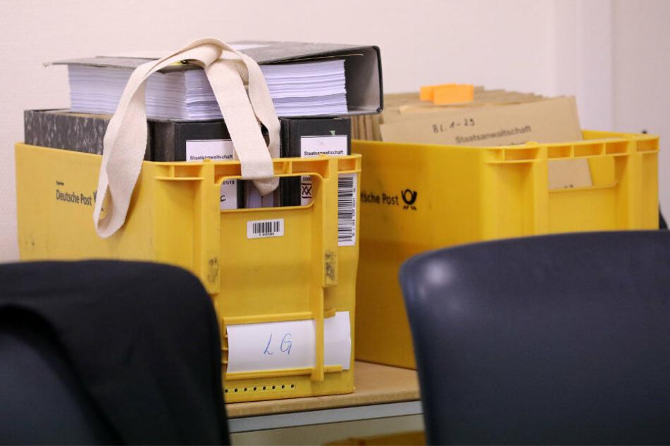Vor Beginn des Prozesses wegen Mordes durch Unterlassen und Misshandlung von Schutzbefohlenen in sieben Fällen stehen Akten in gelben Post-Kisten hinter dem Richtertisch.