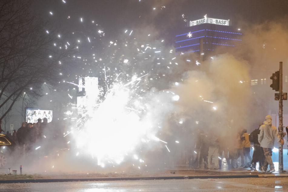 Böller und Raketen steigen auf der Straße an der Oberbaumbrücke in die Luft, während Passanten vorbeigehen.