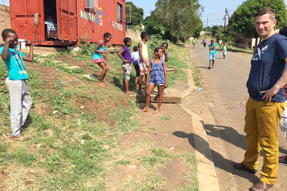 Mitten in der Township: Kinder bestaunen den fremden weißen Minister (r.), der ihre Siedlung besucht. Man beachte den zur Wohnung umgebauten Schiffscontainer (l.).