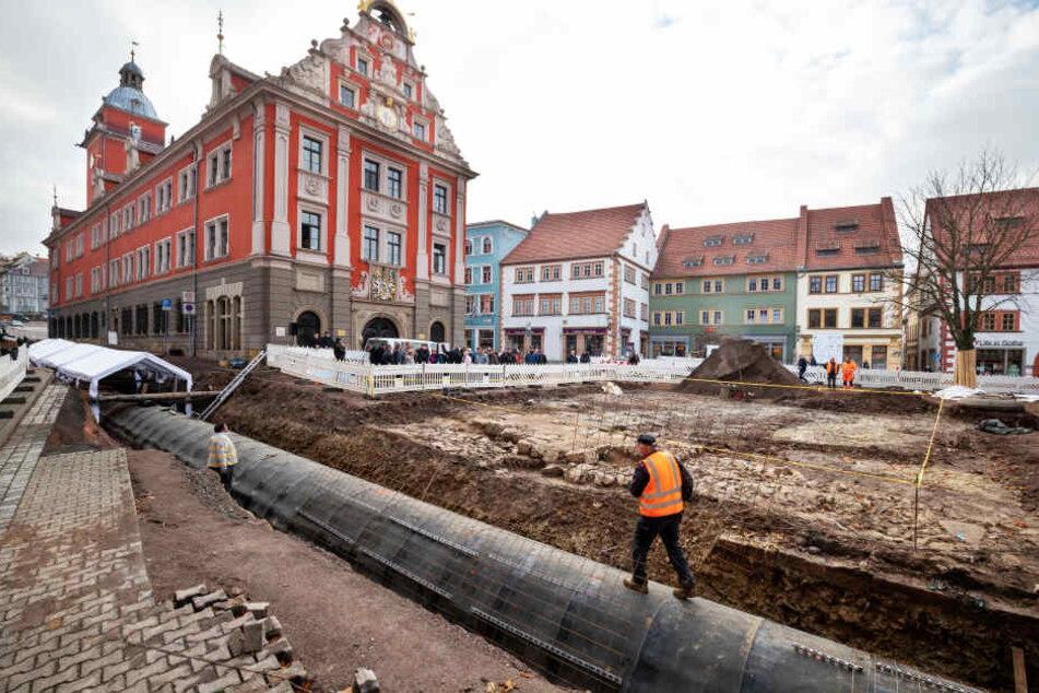 Ein Bauarbeiter läuft auf dem eingehausten Leinakanal, während das Landesamt für Denkmalpflege und Archäologie bei einer Führung die freigelegten Überreste der Jakobskapelle am Gothaer Hauptmarkt vorstellt.