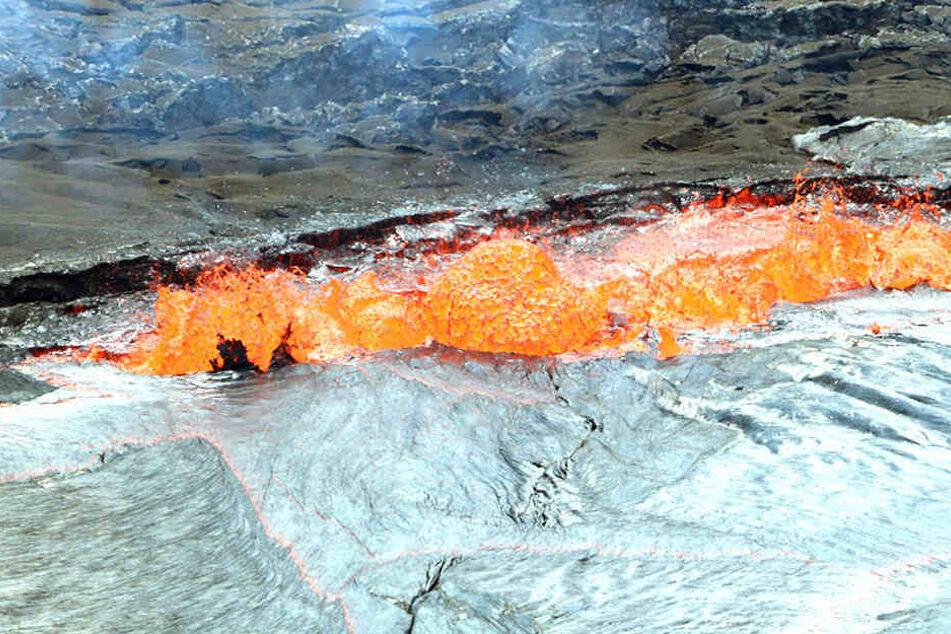 Lava spritzt am Rande eines Kraters nach oben.