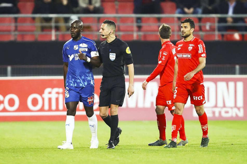 Amiens Kapitän Prince Gouano (l.) wird von Schiedsrichter Karim Abed (Zweiter von links) beruhigt.