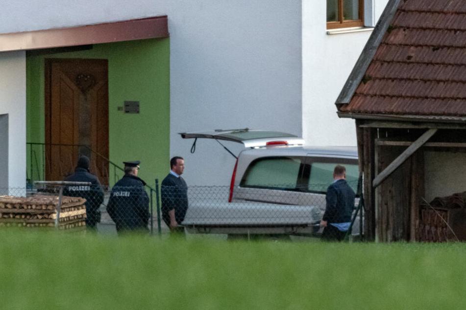 Ein Sarg wird aus dem Wohnhaus getragen. Der angeklagte Sohn soll seine Eltern und seine Schwester hier vor einem halben Jahr getötet haben. (Archivbild)