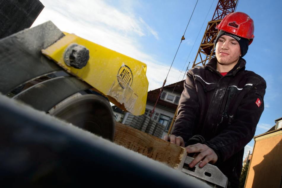 Sven Hofmann, Auszubildender in der Bauwirtschaft zersägt eine Holzleiste.