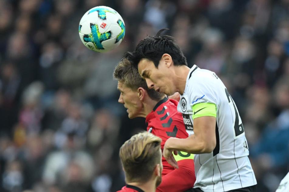 Makoto Hasebe (re.) gewinnt das Kopfball-Duell gegen Nils Petersen.