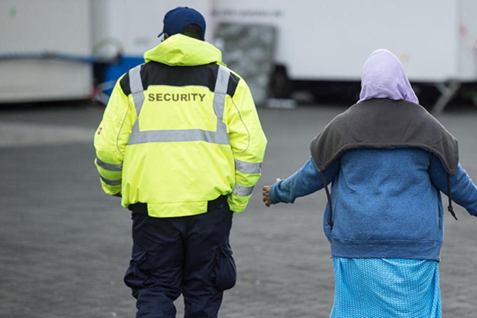 Ein Sicherheitsdienstmitarbeiter begleitet eine Asylbewerberin.