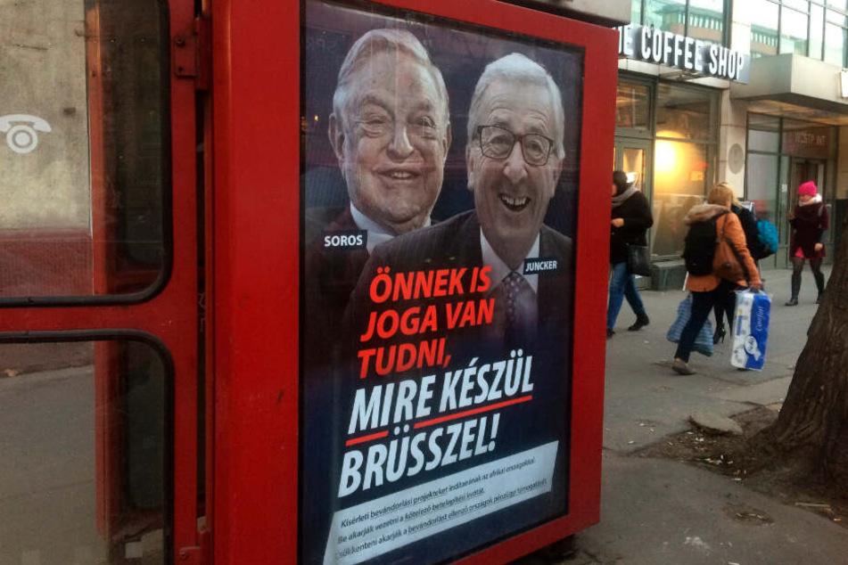 """An einer Telefonzelle in Budapest hängt ein Plakat mit dem ungarisch-amerikanischen Milliardär George Soros und dem Präsidenten der EU-Kommission Jean-Claude Juncker mit der Aufschrift """"Sie haben ein Recht darauf zu wissen, was Brüssel vorhat""""."""
